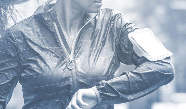 Een sporter met regenjasje is buiten aan het sporten