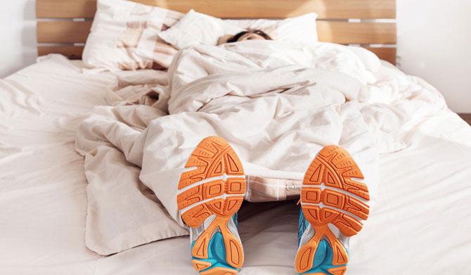 Een persoon meth hardloopschoenen nog aan is aan het rusten in bed