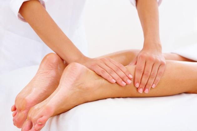 Iemands kuit wordt gemasseerd door een masseur