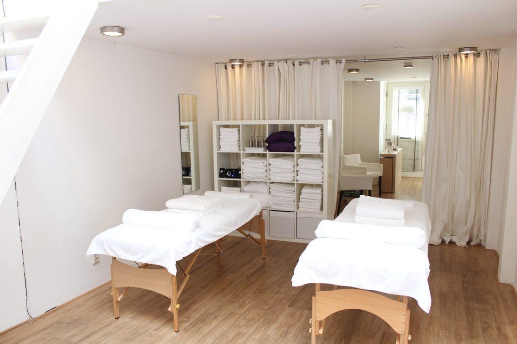 Een massagekamer met twee massagebedden, veel handdoeken en een spiegel